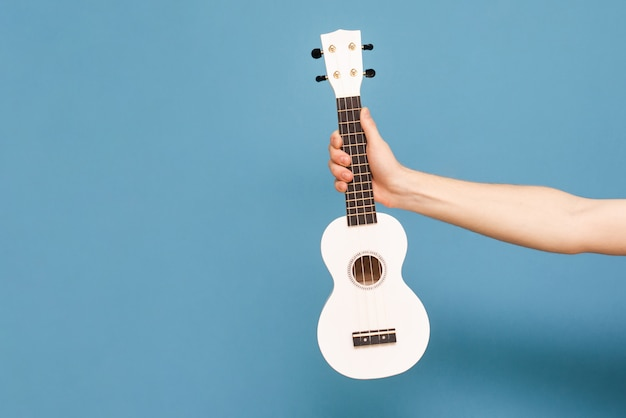 Hand holds ukulele on a blue background. musical concept. music as a hobby.