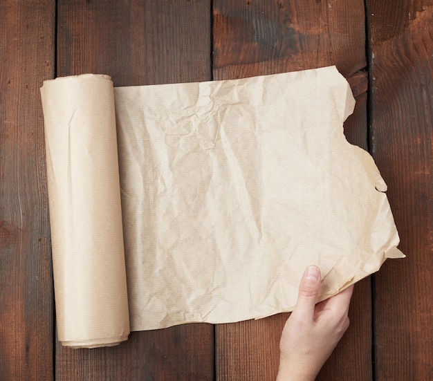 Hand holds unfolded roll with brown parchment paper