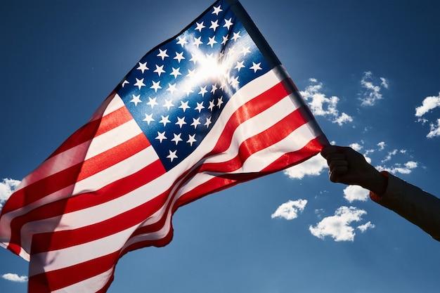 Рука держит национальный флаг сша на фоне голубого облачного неба