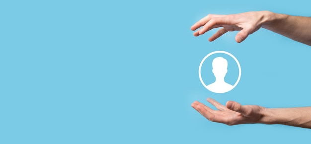 Hand holds user person icon interface on blue surface