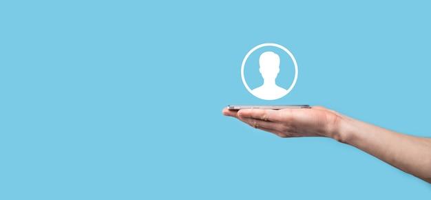Рука держит интерфейс значка лица пользователя на синем фоне. символ пользователя для дизайна вашего веб-сайта, логотип, приложение, ui.banner.