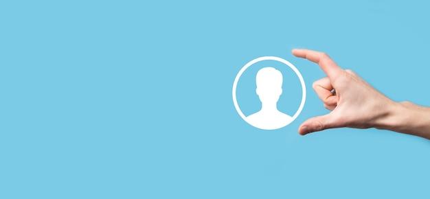 Рука держит интерфейс значка лица пользователя на синей поверхности