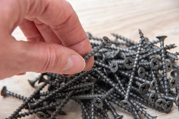 손 나무 표면, 평면도, 근접 촬영, 복사 공간에 다양 한 검은 금속 나사를 보유하고있다.