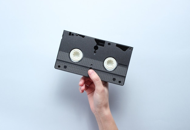 Hand holds video cassette on gray background. retro style, pop culture, minimalism, top view