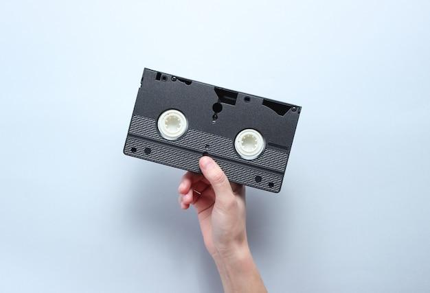 手は、灰色の背景にビデオカセットを保持しています。レトロなスタイル、ポップカルチャー、ミニマリズム、トップビュー
