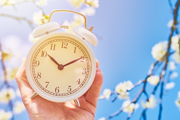 Hand holds vintage alarm clock against blue sky and blooming plant