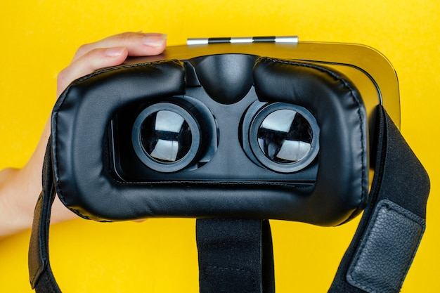 Hand holds a virtual reality helmet ( glasses ) on a yellow background