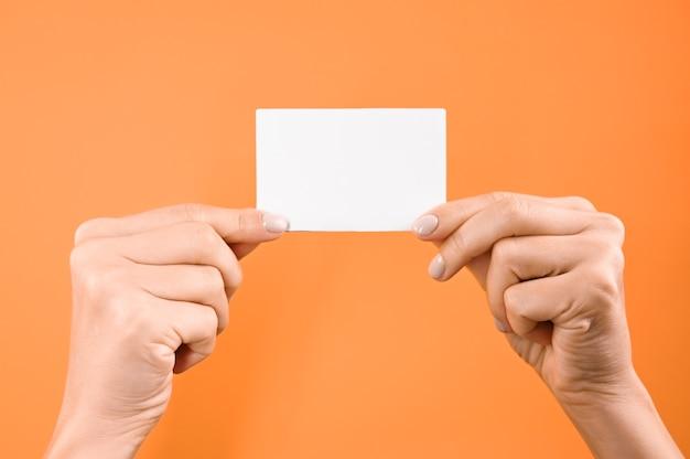 Рука держит белый пустой знак на оранжевом фоне.