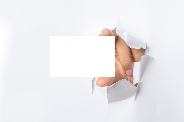 Hand holds white card through white torn paper background