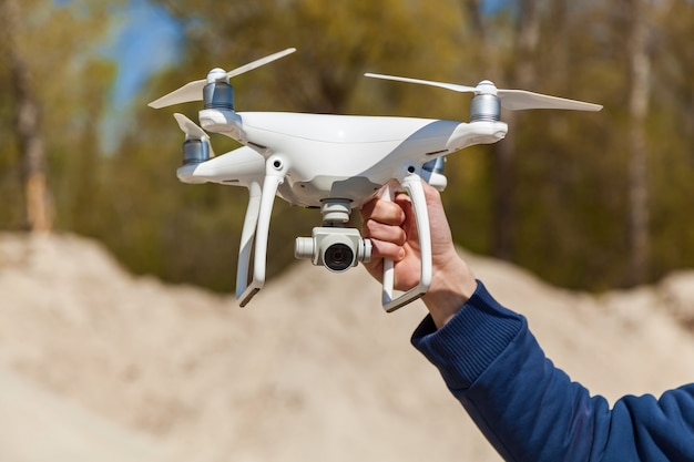 A hand holds white quadcopterquadcopter takes off video and photo of car from air