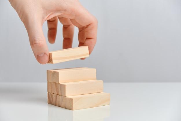 はしごの上に木製のブロックを保持する手