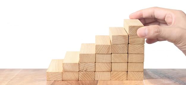 手が白い背景の上の木製のブロックを保持します