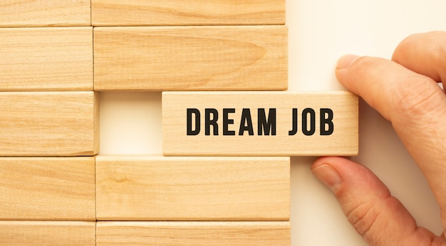Hand holds a wooden cube with the text dream job. positive thinking concept