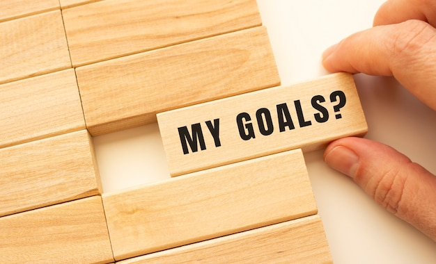 Hand holds a wooden cube with the text my goals