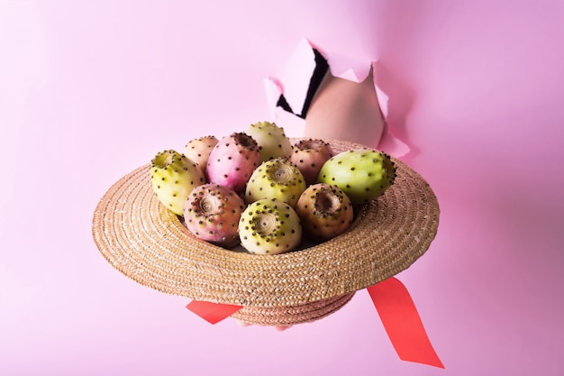 A hand in a hole holds a straw hat with opuntia or prickly pear fruit on a fashionable pink background