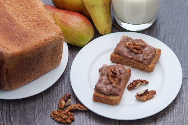 Hand or home made chocolate paste with nuts. healthy snack. milk, pear, bread.