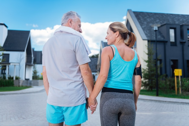 Hand of husband. appealing blonde-haired woman holding hand of her handsome strong man while walking in the morning