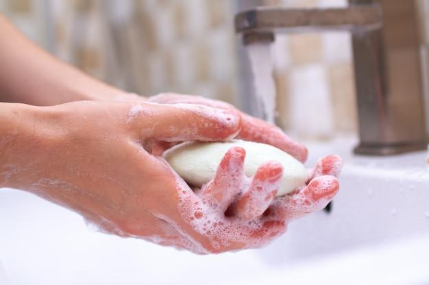 손 위생. 화장실에있는 사람이 비누로 손을 씻고 씻고 있습니다.