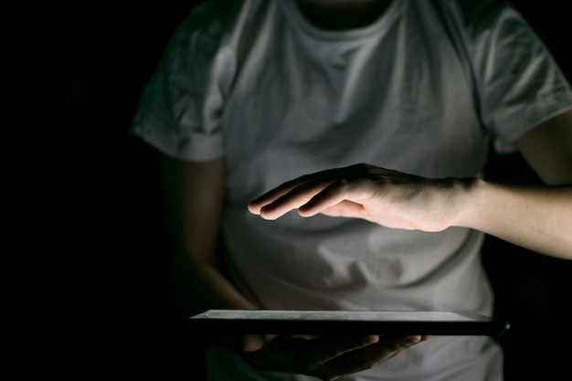 Hand illuminated by the light of a tablet