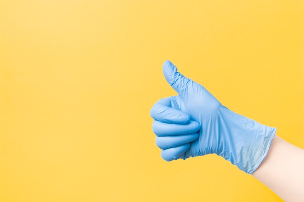 노란색 표면에 제기 엄지 손가락으로 파란색 일회용 의료 장갑에 손을