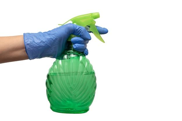 青い手袋の手は、屋内植物で作業するためのスプレーガンを保持し、分離します