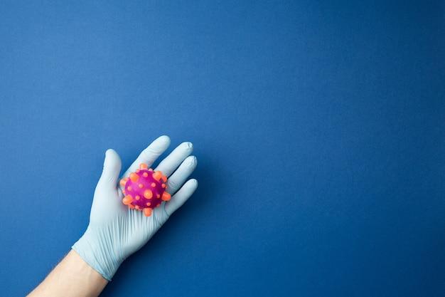 医療用手袋を手に入れて、青い孤立した壁にあるウイルスのモックアップを調べます。パンデミックコントロールの概念。