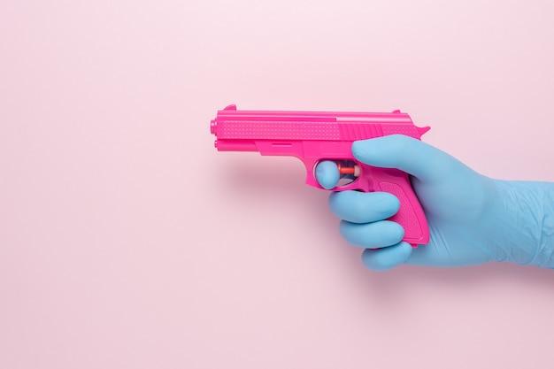 ピンクの背景にピンクの拳銃で医療用手袋を手に