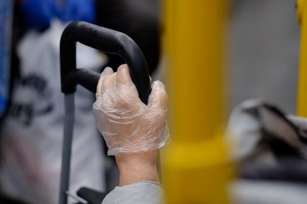 여행 가방의 손잡이를 잡고 있는 플라스틱 장갑에 손을 대고 대중 교통에서 바이러스 보호