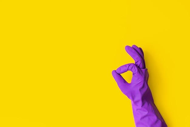黄色の背景に紫色のゴム手袋を手に入れます。クリーニングコンセプト、クリーニングサービス。バナー。フラットレイ、上面図