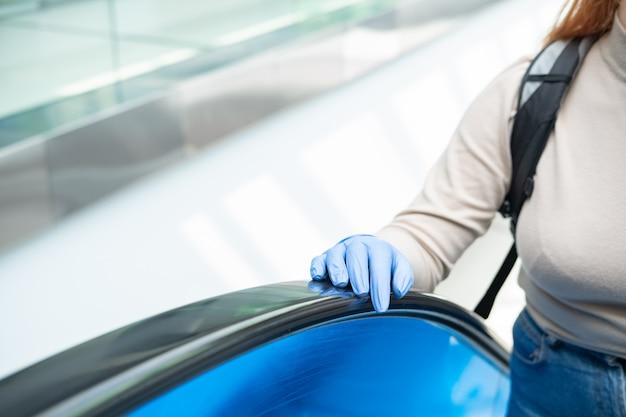 Рука в резиновой перчатке на руле эскалатора.