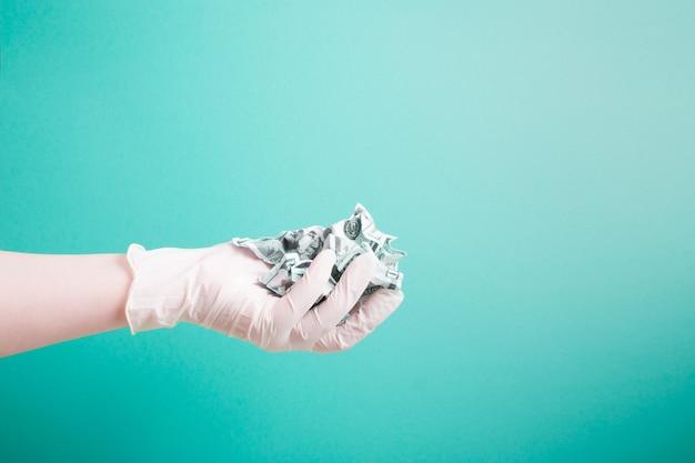 ゴム製の白い医療用使い捨て手袋を手に、緑色の表面にしわくちゃのドル札を保持します
