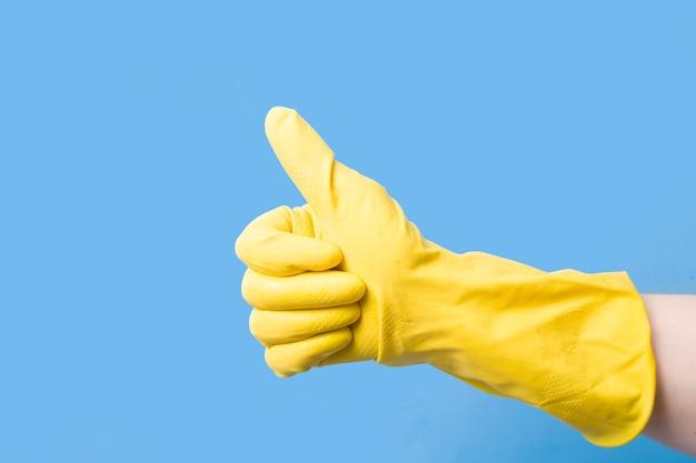 파란색 표면에 위로 올려 진 엄지 손가락으로 청소하기 위해 노란색 고무 장갑을 끼십시오.