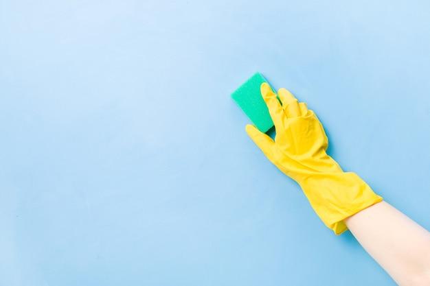 黄色のゴム手袋をはめた手は、皿洗いと掃除のための緑色のスポンジを持っています