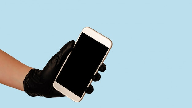 青いスペースに空の空白の画面を持つスマートフォンを保持している黒い手袋で手します。安全な食品配達のコンセプト。