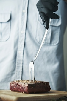 Рука в черной перчатке держит большую стальную вилку с жареным куском мяса на деревянной доске