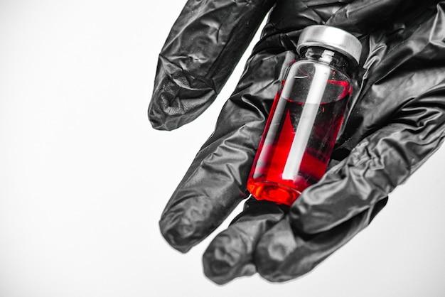黒い手袋をはめた手は、医療用バイアルまたはアンプルを保持します。ワクチン。薬とアンプル。注射薬。