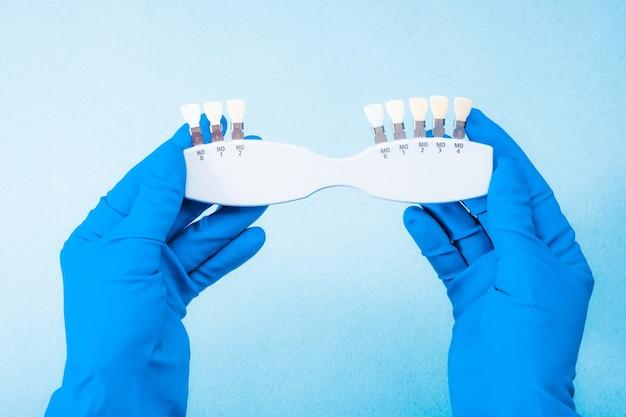 Рука в синей перчатке, держащая стоматологическую цветовую палитру на голубом фоне