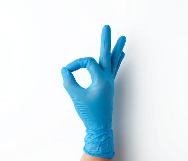 青い医療用手袋で手がokのしぐさ、白い背景を示しています