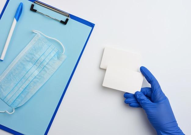 Рука в синих медицинских перчатках держит прямоугольную белую пустую визитку