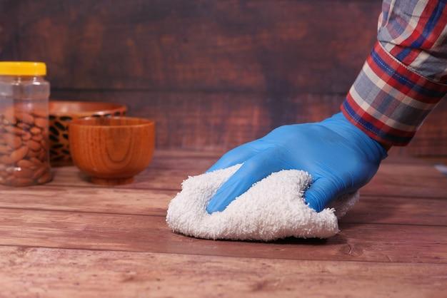 布でテーブルを掃除する青いゴム手袋で手します。