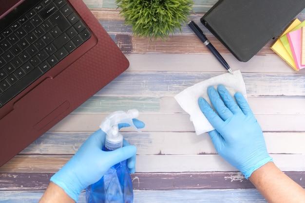스프레이 병 청소 테이블을 들고 파란색 고무 장갑에 손을