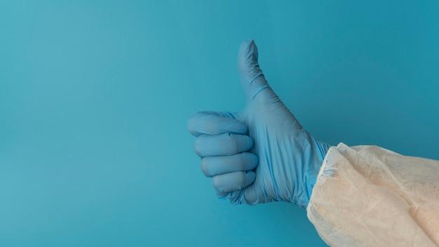 파란색 실리콘 장갑을 끼고 파란색 배경의 보호복은 확인 표시를 보여줍니다.