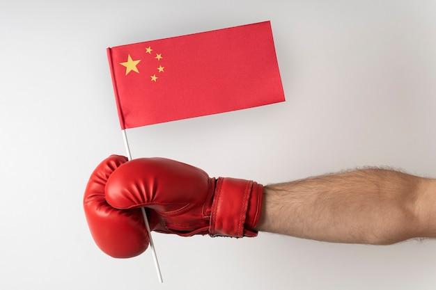 ボクシンググローブの手は中国の旗を握っています。白い背景で隔離。