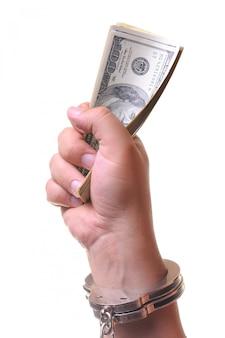 お金を保持している閉じた金属の手錠で手します。