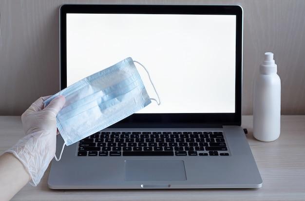 Рука в перчатке держит маску на ноутбуке.