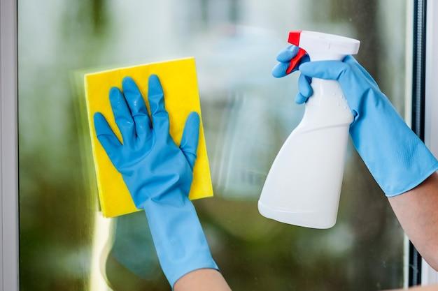 장갑을 낀 손으로 창문을 닦는다.