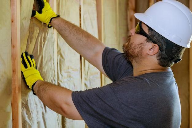 ミネラルウールを保持している手袋で手をロックウールで建設壁断熱材の下に構築