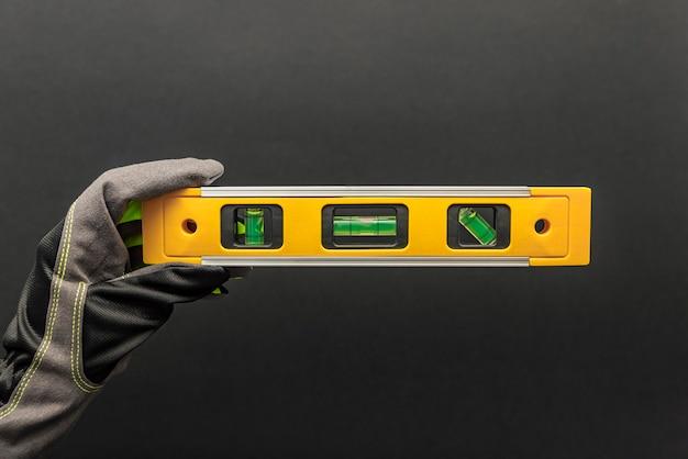 Рука в перчатках держит желтый строительный уровень на черном фоне. открытка или плакат для печати, место для текста.