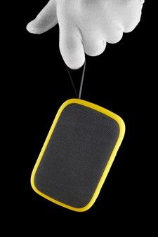Рука в перчатках держит желтый беспроводной динамик