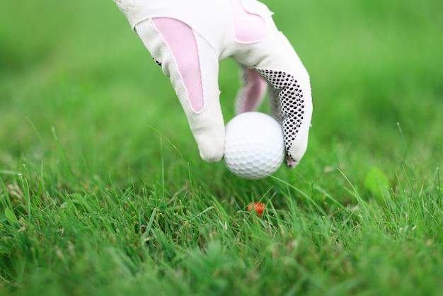 ゴルフグローブを手に持って打つボールを固定
